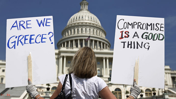 A demonstrator holds placards to protest U.S. debt in front of the Capitol in Washington (Reuters/Kevin Lamarque)