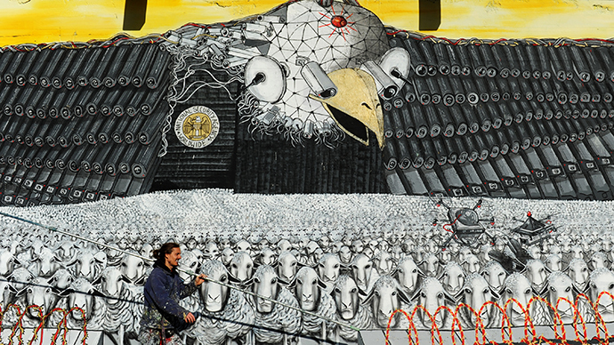 "The group's mural titled ""Surveillance of the fittest"" featuring the emblematic US eagle with a badge that reads ""National Security Agency worldwide"" in Cologne, Germany on October 24, 2013. (AFP Photo / Marius Becker)"