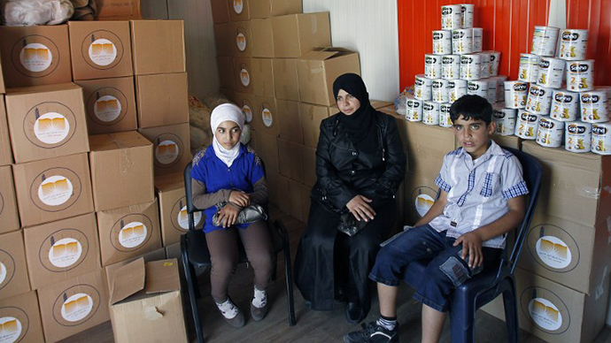 Fadia, a Syrian refugee wife and mother of Syrian rebels, sit near her son Mohamad and daughter Nagham at a charity centre, shortly after they crossed the Lebanese border with Syria on September 4, 2013 in Masnaa. (AFP Photo / Anwar Amro)