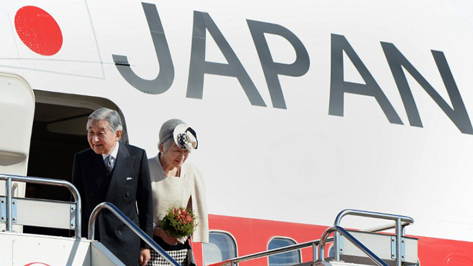 Emperor Akihito (L) and Empress Michiko (R) stand before embarking onto a plane, before they take off for New Delhi, at Haneda Airport in Tokyo on November 30, 2013. (AFP Photo / Toru Yamanaka)