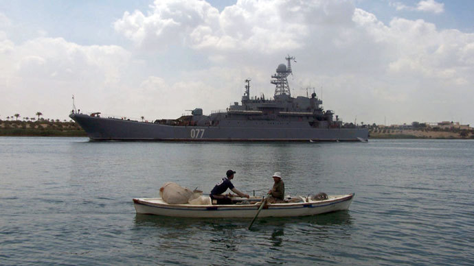 Egyptian fishermen row their boat near the Russian amphibious warfare ship Admiral Nevelsky as it crosses the Suez canal on its way to the Mediterranean sea on May 15, 2013 at Egypt's port town of Ismailia.(AFP Photo / STR)