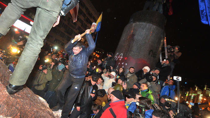 "A protester breaks apart a statue of Lenin at a monument in his honor after it was pulled down during a mass rally called ""The March of a Million"" in Kiev's Independence Square on December 8, 2013. (AFP Photo / Genya Savilov)"