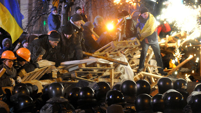 Anti-Yanukovych protesters defend their barricades in front of anti-riot police on Independence Square in Kiev, early on December 11, 2013. (AFP Photo/Victor Drachev)