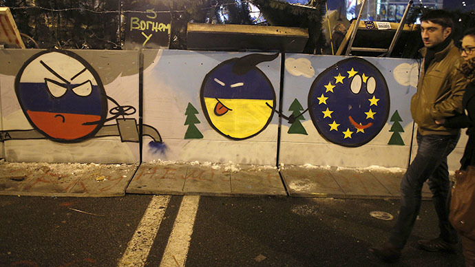 A couple walks by graffiti drawn on a barricade at Independence Square in Kiev (Reuters / Stoyan Nenov)