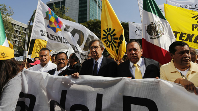 Cuauhtemoc Cardenas (C), founder of the Party of the Democratic Revolution (PRD), and party's president Jesus Zambrano (2nd R) march against the energy reform bill at the Angel of Independence in Mexico City December 10, 2013. (Reuters/Tomas Bravo)