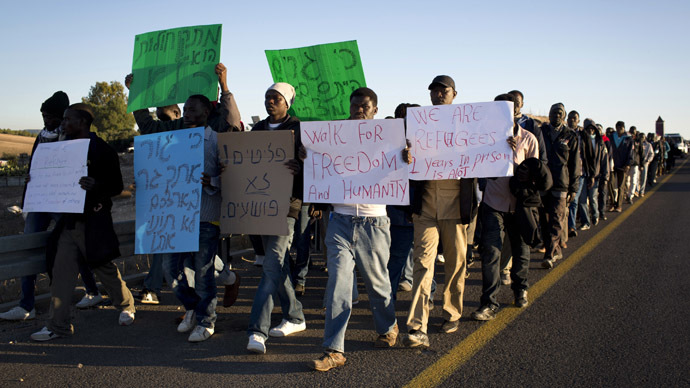 African illegal immigrants take part in a protest march on the highway near Lahav junction in southern Israel on their way to Jerusalem on December 16, 2013 after they fled a detention centre in the south where they were being held.  (AFP Photo/Oren Ziv)