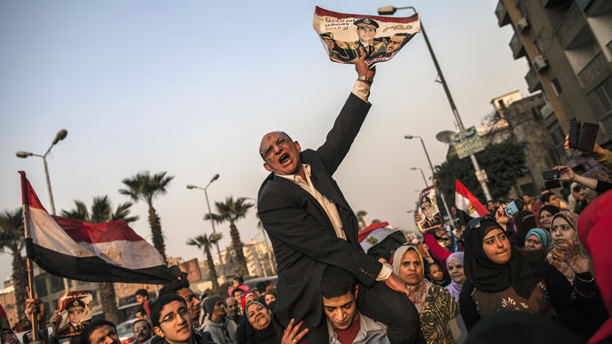 An Egyptian man holds a portrait of Egypt's Defence Minister General Abdel Fattah al-Sisi outside a polling station during the vote on a new constitution on January 14, 2014 in Giza, Cairo (AFP Photo / Mahmoud Khaled)