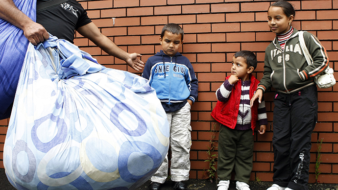 Romanian children are moved along by their father as he arrives with some of their possessions at the Ozone Leisure Centre in East Belfast (Reuters / Cathal McNaughton)