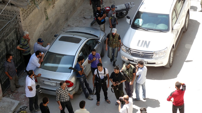 Opposition fighters, civilians and journalists stand near a United Nations (UN) vehicle as UN arms experts inspect the site where rockets had fallen in Damascus' eastern Ghouta suburb on August 28, 2013, during an investigation into a suspected chemical weapons strike. (AFP Photo / Mohamed Abdullah / Shaam News Network)