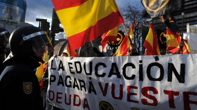 Far-right students wave Spanish flags and hold a banner in front of policemen as they protest against government's austerity measures in Madrid on March 14, 2013. (AFP Photo)