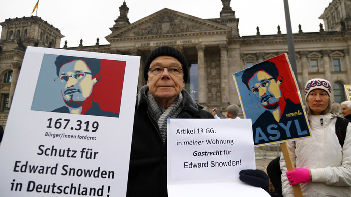 A demonstrator supporting fugitive former U.S. National Security Agency contractor Edward Snowden, holds up a banner outside the Reichstag building, the seat of the German lower house of parliament Bundestag in Berlin November 18, 2013. (Reuters/Tobias Schwarz)