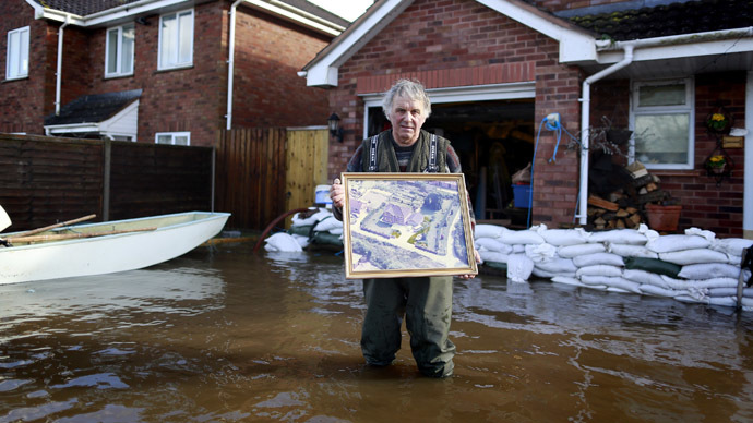 Builder Derek Bristow, 64, poses outside his house with one of the photos he will rescue first if the flood water rises any further in his house, in the flooded Somerset village of Moorland February 16, 2014. (Reuters/Cathal McNaughton)
