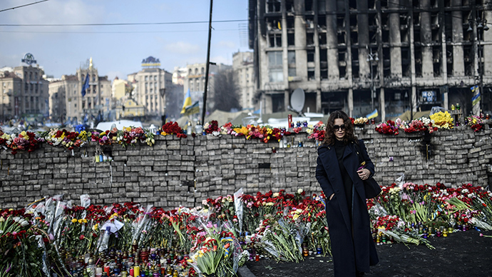A woman stands near a makeshift memorial in homage to anti-government protesters killed in the past weeks' clashes with riot police on Kiev's Independence Square on February 24, 2014 (AFP Photo / Bulent Kilic)