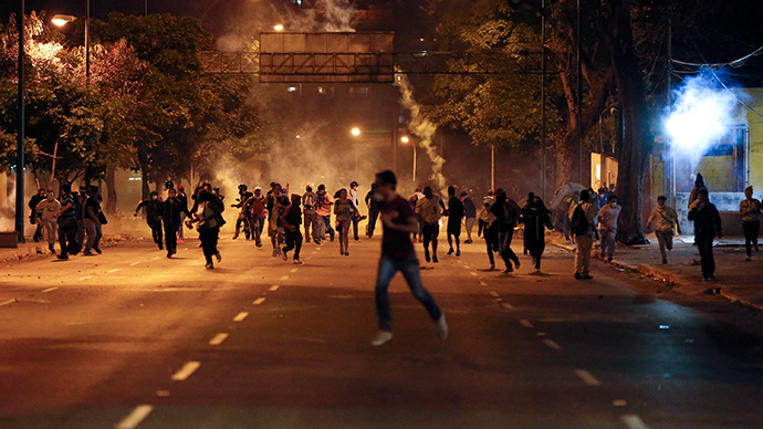 Anti-government demonstrators run from tear gas during clashes with riot police at Altamira Square in Caracas February 24, 2014 (Reuters / Carlos Garcia Rawllins)