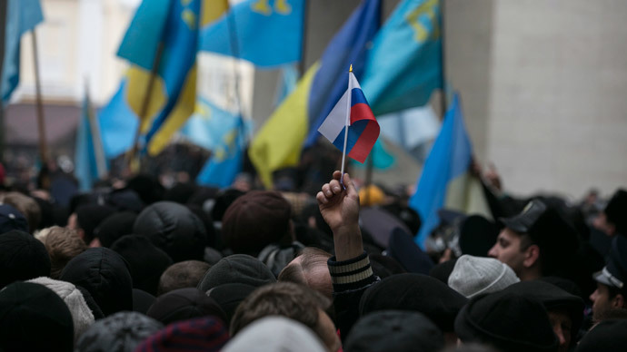 An ethnic Russian Ukrainian holds a Russian flag as Crimean Tatars rally near the Crimean parliament building in Simferopol February 26, 2014. (Reuters / Baz Ratner)