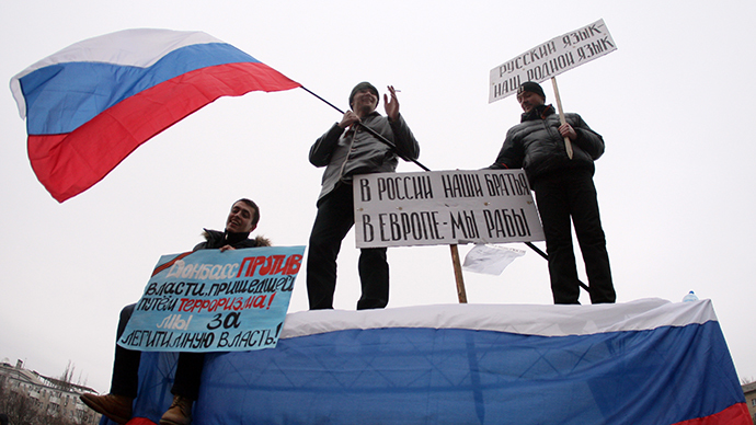 "Pro-Russian protesters wave a Russian flag and hold a sign (C) reading ""Our brothers are in Russia, we are slaves in Europe"" during a rally in front of the regional administration building in the industrial Ukrainian city of Donetsk on March 1, 2014. (AFP Photo / Alexander Khudoteply)"
