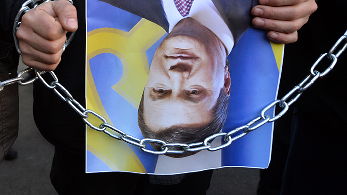 "Protesters hold rotated photos of Ukrainian President Viktor Yanukovych  and signed ""Upside down "" (in Ukrainian the word has as well another meaning: overturn and revolution) during the protest action at the Internal Affairs Ministry in Kiev on December 26, 2013 (AFP Photo / Sergei Supinsky)"