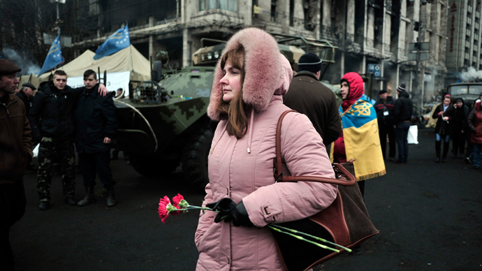 A woman holding carnations walks on Independence (Maidan) square in central Kiev on February 25, 2014 (AFP Photo / Louisa Gouliamaki)
