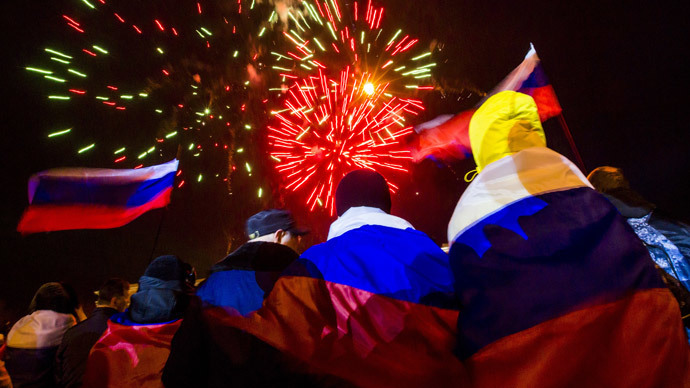 People wrapped with Russian flags watch fireworks during celebrations after the preliminary results of today's referendum are announced on Lenin Square in the Crimean capital of Simferopol March 16, 2014.( Reuters / Thomas Peter)