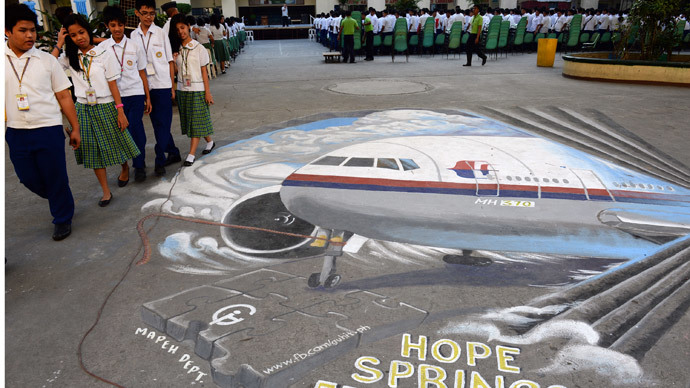 Students walk past a giant mural featuring missing Malaysia Airlines flight MH370 displayed on the grounds of their school in Manila's financial district of Makati on March 18, 2014 (AFP Photo / Ted Aljibe)