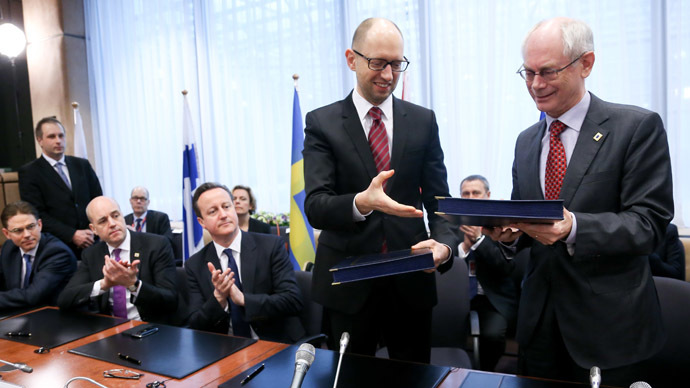 European Council president Herman Van Rompuy (R) exchanges documents with Ukrainian Prime Minister Arseniy Yatsenyuk during the signing of the political provisions of the Association Agreement with Ukraine at the EU headquarters in Brussels on March 21, 2014 on the second day of a two-day European Council summit. (AFP Photo)