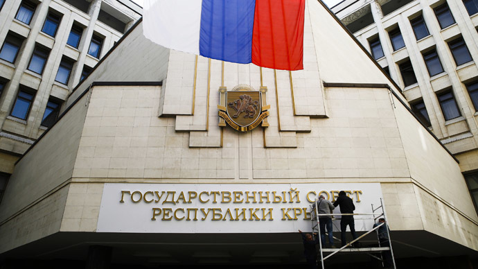 Workers put up a new sign at the local parliament building in Simferopol March 19, 2014. (Reuters)