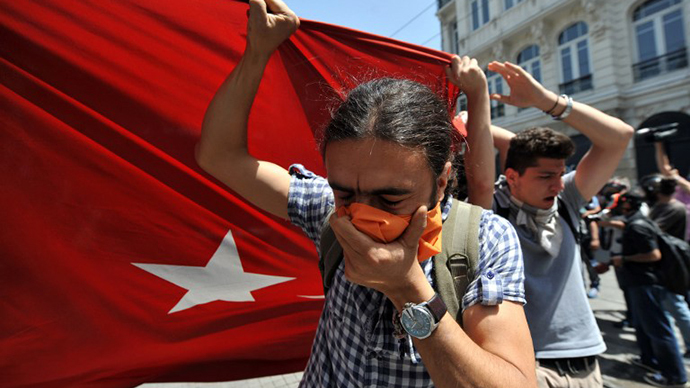Protestors hold a giant Turkish flag in front of a water cannon truck on May 31, 2013 during a protest against the demolition of Taksim Gezi Park, in Taksim Square in Istanbul. (AFP Photo / Ozan Kose)