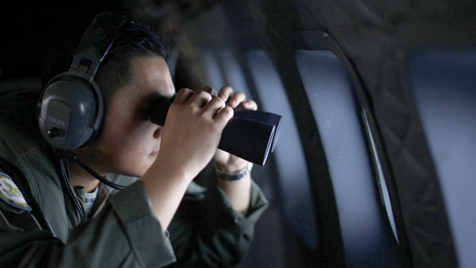 A crew member from the Royal Malaysian Air Force uses binoculars onboard a Malaysian Air Force CN235 aircraft during a Search and Rescue (SAR) operation to find the missing Malaysia Airlines flight MH370, in the Straits of Malacca March 13, 2014. (Reuters)