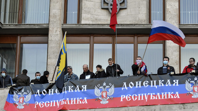 Pro-Russian protesters hang a banner and wave flags as they storm the regional government building in Donetsk April 6, 2014. (Reuters)