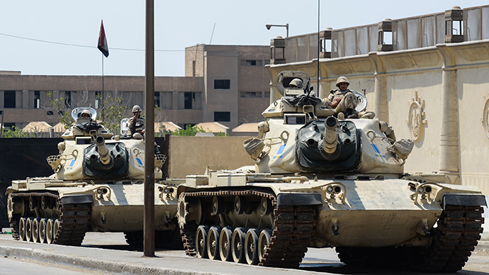 Egyptian military tanks are positioned outside the police institute near Cairo's Turah prison during the trial of three detained journalists with the Qatar-based Al-Jazeera broadcaster on April 10, 2014. (AFP Photo / Mohamed El-Shahed)