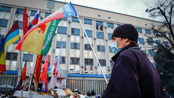 An anti-government protester waves a flag in front of the seized office of the SBU state security service in Luhansk, eastern Ukraine April 14, 2014. (Reuters / Shamil Zhumatov)