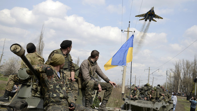 Ukrainian servicemen look at a Ukrainian military jet fly above them while they sit on top of armoured personnel carriers in Kramatorsk April 16, 2014. (Reuters/Maks Levin)