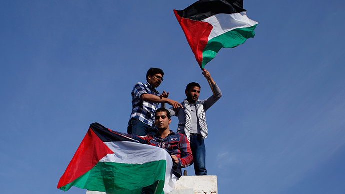 Palestinians hold national flags as they celebrate after an announcement of a reconciliation agreement in Gaza City April 23, 2014 (Reuters / Ibraheem Abu Mustafa)