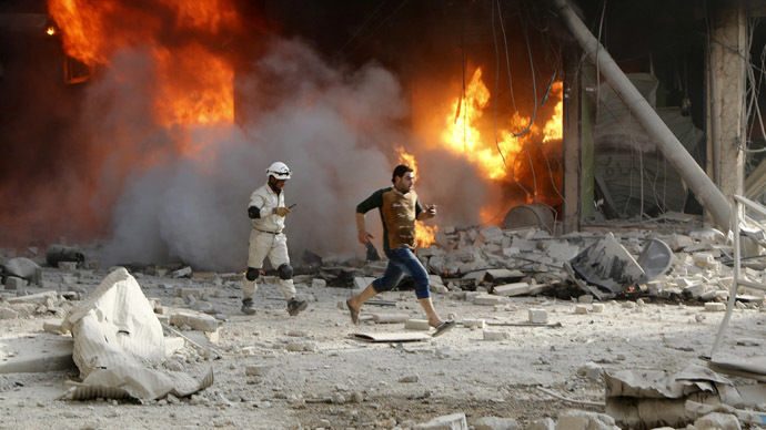 A member of the Civil Defence and a resident pass a fire at a site hit by what activists said were barrel bombs dropped by forces loyal to Syria's President Bashar al-Assad in Aleppo's al-Shaar district April 24, 2014.  (Reuters/Hosam Katan)