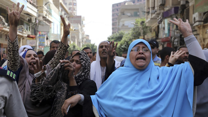 Relatives and families of supporters of ousted President Mohamed Mursi do the Rabaa sign near security forces, after hearing the sentence handed to Muslim Brotherhood leader Mohamed Badie and other Brotherhood supporters, at the court in Minya, south of Cairo April 28, 2014. (Reuters)