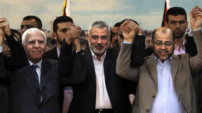 (From L to R) Palestinian Fatah delegation chief Azzam al-Ahmed, Hamas prime minister in the Gaza Strip Ismail Haniya and Hamas deputy leader Musa Abu Marzuk pose for a photo as they celebrate in Gaza City on April 23, 2014 after West Bank and Gaza Strip leaders agreed to form a unity government within five weeks as peace talks with Israel face collapse. (AFP Photo)