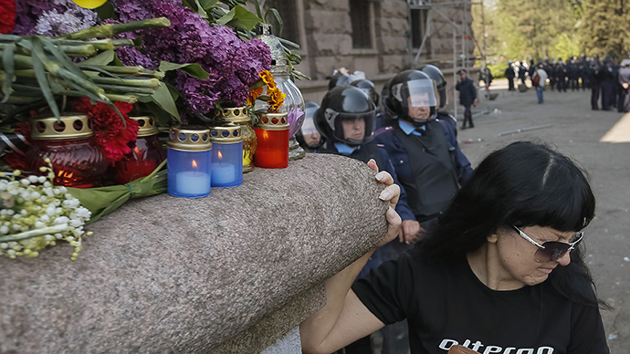 A woman stands next to flowers and lit candles placed in memory of people killed in recent street battles outside a trade union building in Odessa, May 3, 2014. (Reuters / Gleb Garanich)