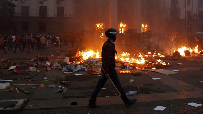 A protester walks past a burning tent camp and a fire in the trade union building in Odessa May 2, 2014. (Reuters / Yevgeny Volokin)