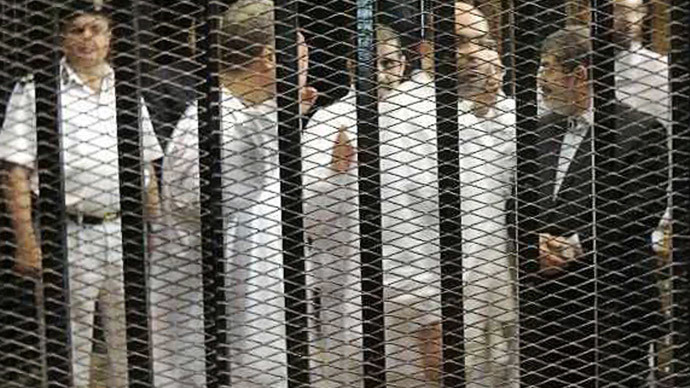 Ousted former Egyptian president Mohamed Mursi (R) speaks with other senior figures of the Muslim Brotherhood in a cage in a courthouse on the first day of his trial, in Cairo, November 4, 2013. (Reuters / Stringer)