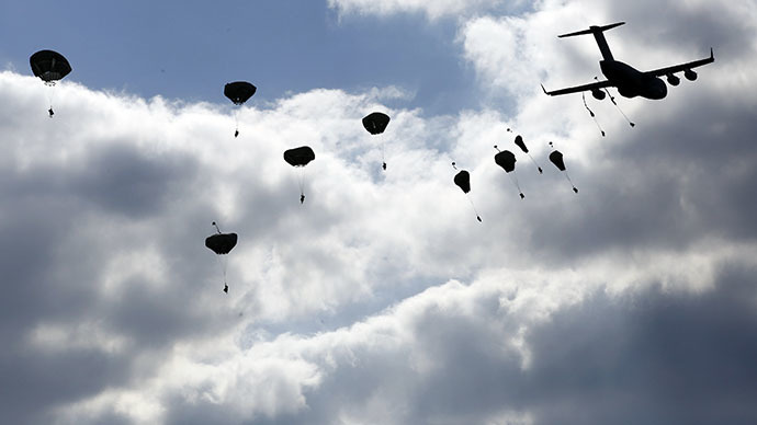 "Troops from the U.S. Army's 173rd Infantry Brigade Combat Team parachute from a Boeing C-17 Globemaster III during a NATO-led exercise ""Orzel Alert"" held together with Canada's 3rd Battalion and Princess Patricia's Light Infantry, and Poland's 6th Airborne Brigade in Bledowska Desert in Chechlo, near Olkusz, south Poland May 5, 2014. (Reuters / Kacper Pempel)"
