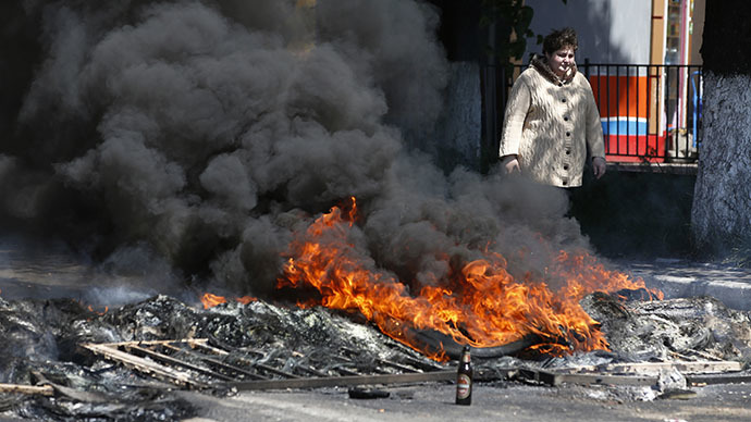 A woman walks past a burning barricade near the city hall in Mariupol, eastern Ukraine May 10, 2014. (Reuters / Marko Djurica)