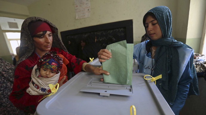 An Afghan woman carrying a child casts her vote at a polling station in Adraskan district, Herat province April 5, 2014. (Reuters/Mohammad Ismail)