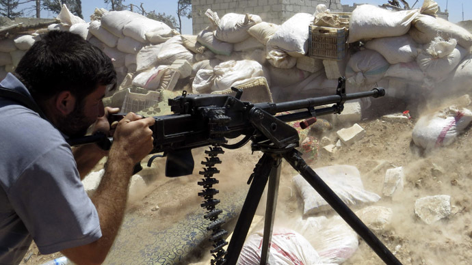 A Free Syrian Army fighter fires his weapon towards forces loyal to Syria's President Bashar al-Assad in Mork, northern Hama countryside May 18, 2014. Picture taken May 18, 2014. (Reuters)