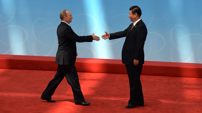 Russian President Vladimir Putin (L) is greeted by Chinese President Xi Jinping before the opening ceremony at the Expo Center at the fourth Conference on Interaction and Confidence Building Measures in Asia (CICA) summit in Shanghai on May 21, 2014. (AFP Photo / Mark Ralston)