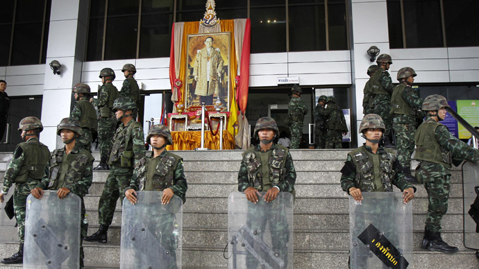 Thai soldiers stand guard at the criminal court in front of a portrait of Thailand's King Bhumibol Adulyadej in Bangkok May 26, 2014. (Reuters)
