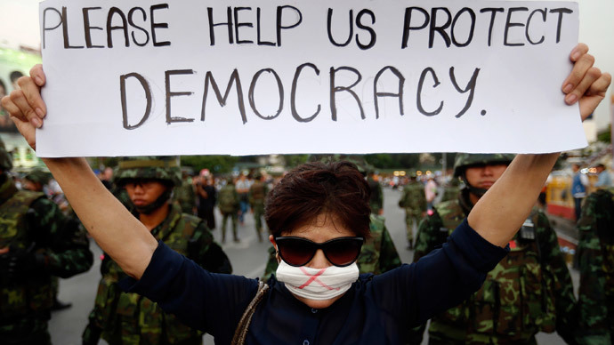 A protester against military rule holds a sign in front of soldiers deployed to the Victory monument where protesters are gathered, in Bangkok May 26, 2014. (Reuters / Damir Sagolj)