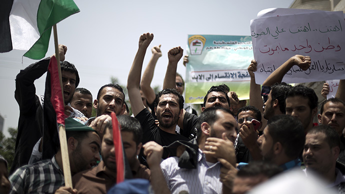 Palestinian protesters chant slogans to speed up the implementation of the national reconciliation and the announcement of the formation of a national unity government, during a rally in Gaza City on May 27, 2014. (AFP Photo / Mohammed Abed)