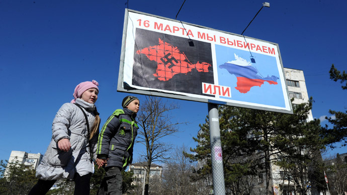 "Children walk past a billboard sign in Sevastopol on March 13, 2014, reading ""On March 16 we will choose either... or..."" and depicting Crimea in red with a swastika and covered in barbed wire (L) and Crimea with the colors of the Russian flag. (AFP Photo / Viktor Drachev)"