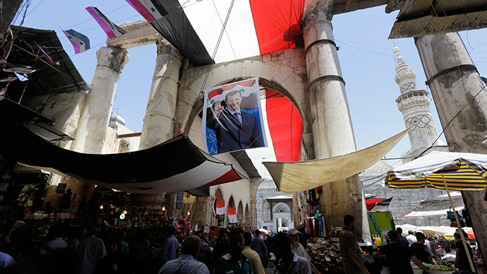 Syrians walk under a giant campaign billboard bearing the portrait of Syrian President Bashar al-Assad on June 1, 2014 in the Hamidiyeh popular market in the capital Damascus (AFP Photo / Joseph Eid)