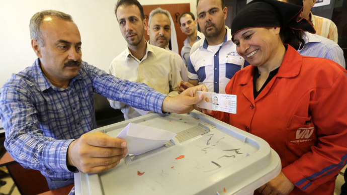Syrians cast their ballots in the Syrian presidential elections at a polling station in the city of Homs, north of Damascus, on June 3, 2014. (AFP Photo/Joseph Eid)